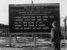 Un soldato britannico legge un cartello delle forze britanniche all'ingresso del campo di concentramento di Bergen-Belsen, Germania, 1945