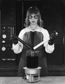 Un tecnico di laboratorio solleva due bacchette di plastica da un bagno bollente di acido solforico caldo per dimostrare il Teflon appena inventato, anni '40