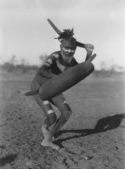 Uomo Luritja dimostra il metodo di attacco con boomerang sotto copertura di uno scudo, Australia centrale, 1920