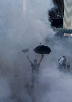Un dimostrante democratico tiene un ombrello dopo che la polizia ha lanciato gas lacrimogeni verso i manifestanti durante l'Umbrella Revolution