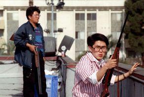 Due uomini coreani stanno sul tetto di un negozio di alimentari con i fucili per impedire ai saccheggiatori di entrare nel negozio. Los Angeles, 30 aprile 1992