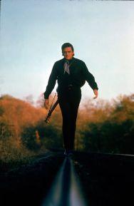 Johnny Cash che cammina lungo la linea di una pista ferroviaria con la sua chitarra legata tra le spalle, 1969. Fotografie di Michael Rougie