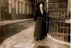Una suffragetta che si incatena alle inferriate per protesta nei primi anni del 1900