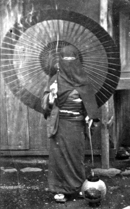 Donna in un abito invernale con ombrello. Nagasaki, Giappone. 1868
