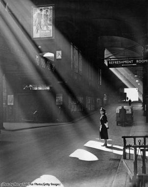 I raggi del sole primaverile illuminano una poliziotta della ferrovia a Liverpool Street Station, Londra, 1952