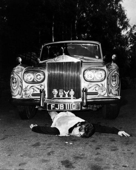 John Lennon, finge di essere stato investito dalla sua psichedelica Rolls-Royce. In un presagio inquietante i suoi iconici occhiali da vista giacciono davanti a lui sul pavimento (1967)