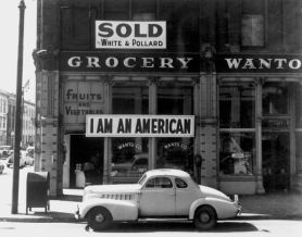 Un americano giapponese spiegò questo stendardo sulla sua attività il giorno dopo l'attacco di Pearl Harbor, 1942. Fotografato da Dorothea Lange poco prima dell'internamento dei proprietari