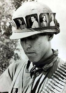 Un soldato americano tiene un ricordo costante della sua ragazza a casa, col suo elmetto pieno delle sue fotografie. Vietnam, 1968