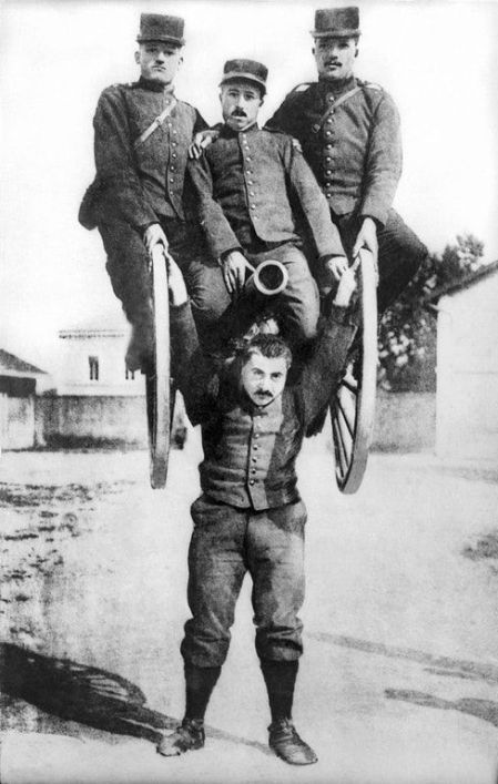 Un uomo forte nell'esercito francese che solleva con la testa un cannone e tre dei suoi compagni, (1917)