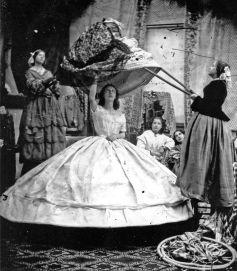 Una donna che indossa crinolina è vestita con l'aiuto di lunghi pali per sollevare il vestito sopra i cerchi, Londra, ca. 1860