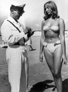 Un poliziotto che fa una multa a una donna perché indossa un bikini su una spiaggia a Rimini, Italia, 1957
