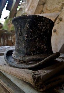 Un cappello a cilindro dimenticato tra le rovine di una casa