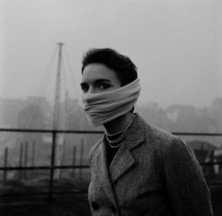 Una signora con fili di perle intorno al collo e una sciarpa di chiffon attorno al naso e alla bocca durante il Grande Smog (Londra, 1952)
