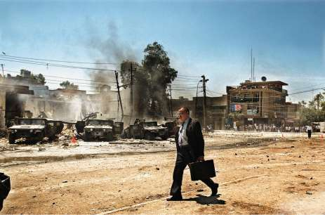 Baghdad, 2004. Gli iracheni camminano sulla scena dell'attacco dell'esercito americano, che ha preso vite umane nel quartiere Al-Waziriya di Baghdad
