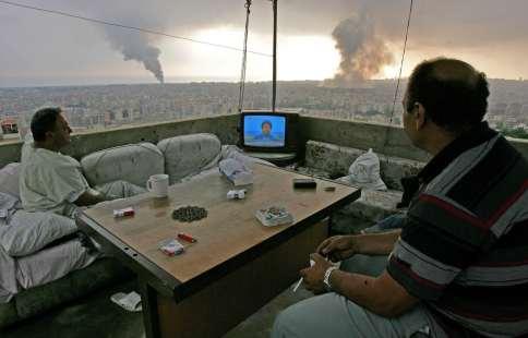 Beirut, 2006. Cittadini libanesi guardano il leader di Hezbollah Sheik Hassan Nasrallah in TV, osservando come il fumo nero si alza dopo l'attacco di Israele nella periferia sud della città