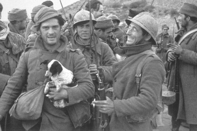 George Orwell tiene un cucciolo durante la guerra civile spagnola nel 1937. Ernest Hemmingway nello sfondo