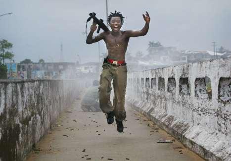 Monrovia, 2003. Il comandante della milizia liberiana esulta dopo aver sparato le granate con propulsione a razzo contro i ribelli