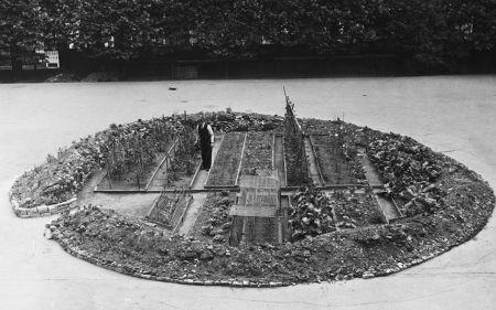 Un giardiniere nel parco della Cattedrale di Westminster che innaffia le verdure in un appezzamento formato da un cratere lasciato dopo un'incursione aerea tedesca