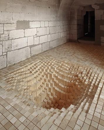 Installazione architettonica di 3000 cubi di legno disposti nell'illusione di un buco affondante, di Fanny Bouchet & Emmanuelle Messier