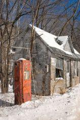 Stazione di servizio abbandonata nella neve e nella luce solare di inverno lungo il bordo della strada, americana rustica degli anni 60