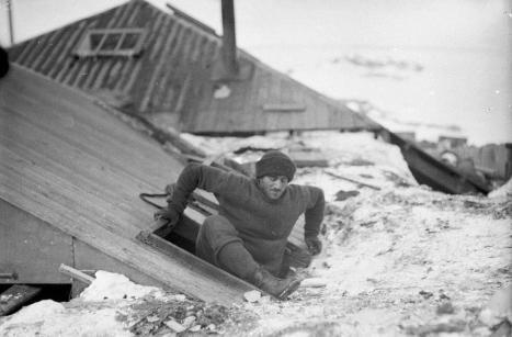 Xavier Mertz che esce dalla cabina attraverso la botola sul tetto della terrazza. Fotografia di Frank Hurley