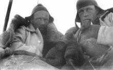Wild & Watson nei loro sacchi a pelo all'interno di una tenda durante una giornata in slitta. Fotografia di Frank Hurley