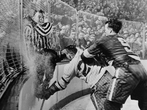 Gordie Howe dei Detroit Red Wings, tira Frank Udvari mentre l'arbitro scappa dalla collisione. 1956