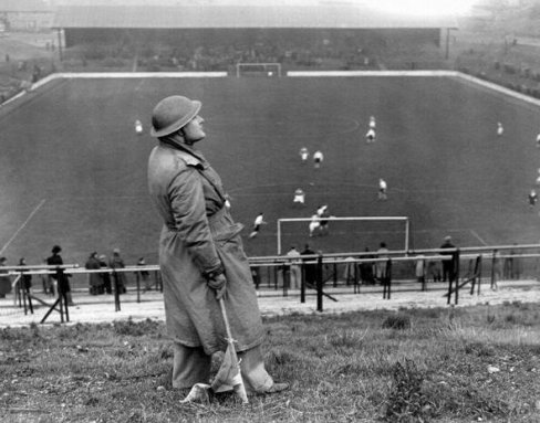 Uno spotter guarda in cielo per incursioni aeree tedesche, durante il match Charlton Athletic vs Arsenal a The valley, Londra 1940