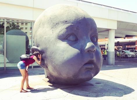 """Madrid day-by-day - Cabeza de niño - (Dia) """"Aspetta a crescere bambino, goditi l'infanzia e, se puoi, portala con te sempre. In fondo in questo risiede la tua possibilità di essere felice..."""" (L'Estación De Atocha ospita due sculture dell'artista Antonio López. Son due grandi teste di bambino, una chiamata giorno e una notte. Nella prima il bambino ha gli occhi aperti, nell'altra dorme) - Cabeza de niño - Dia"""