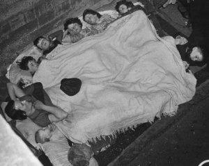 Bambini e adulti condividono una coperta mentre dormono al loro rifugio antibomba nel sud-ovest di Londra, 1940