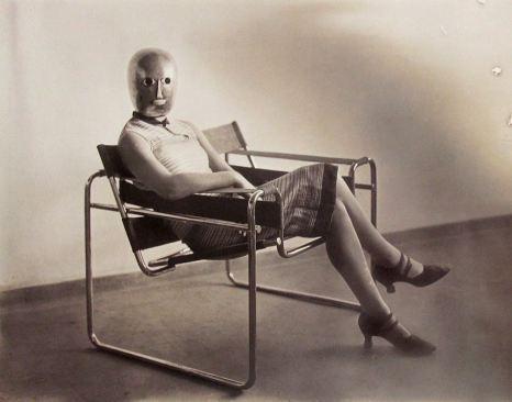 Una donna non identificata che indossa una maschera di Oskar Schlemmer, seduta in una sedia Wassily di Marcel Breuer, c. 1926