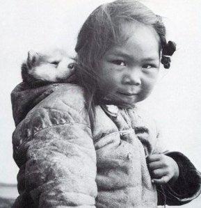 Piccola ragazza Inuit e il suo husky. Foto di Richard Harrington, 1950