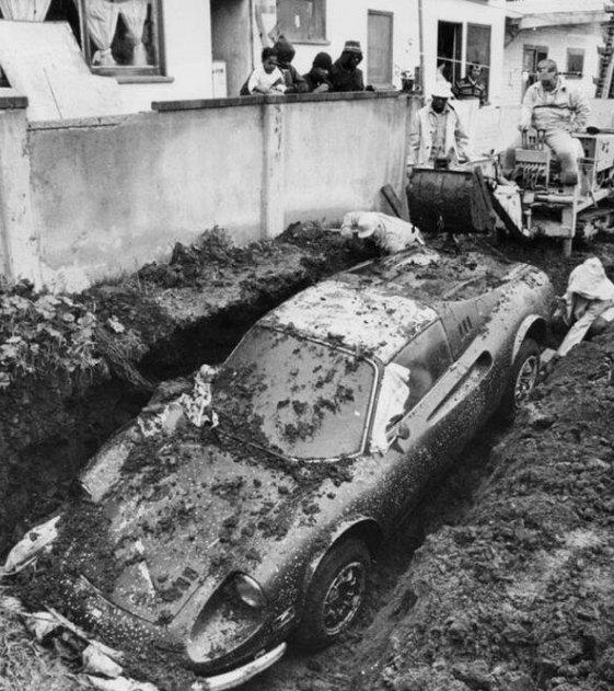 Operai rimuovono una Ferrari trovata sepolta nel cortile di una casa a Los Angeles. L'auto era stata segnalata come rubata nel 1974