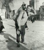 Un uomo con una pecora alle spalle in un mercato di pecore in Turchia, negli anni '30