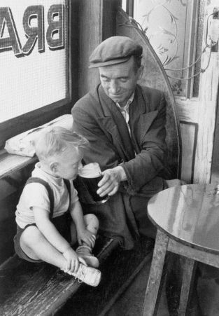 Un uomo che condivide una pinta con suo figlio in un pub irlandese, anni '50