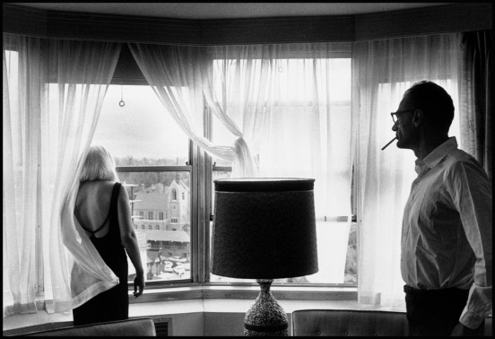 """USA. Reno, Nevada. 1960. Set of """"The Misfits"""". Marilyn Monroe and Arthur Miller in their suite in Reno's Mapes Hotel after a day's shooting."""