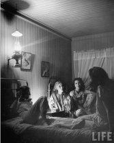Ragazze che siedono sui letti e parlano alla luce delle lampade a cherosene. New York, 1945. Fotografia di Nina Leen