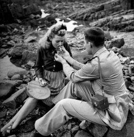 Un aviatore della Marina degli Stati Uniti e una ragazza fumano sulla costa del Marocco. Casablanca, 1943