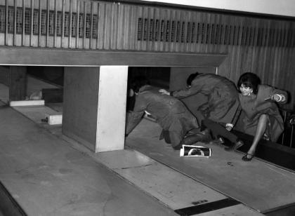 Tre fan dei Beatles tentano di entrare nella Customs Hall dell'aeroporto di Londra strisciando sul nastro trasportatore del bagaglio, 1964