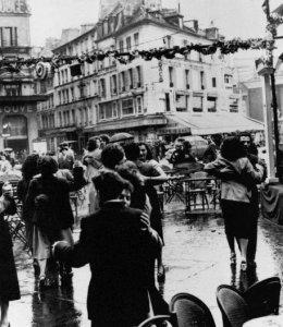 Coppie ballano per le strade di Parigi sotto la pioggia per celebrare il 14 luglio, festa nazionale della Francia. 1954