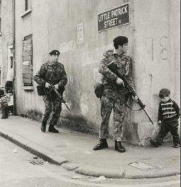 Un ragazzino che cammina verso i suoi amici incontra soldati britannici dietro l'angolo a Belfast, nell'Irlanda del Nord. 1973