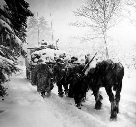 Truppe della 82a divisione aviotrasportata degli Stati Uniti in marcia dietro il carro armato M4 Sherman in una tempesta di neve, Belgio, 28 gennaio 1945