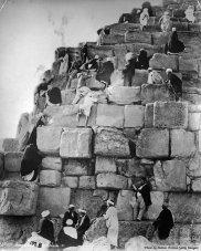 Turisti e guide si arrampicano sulle lastre di roccia di una piramide, in Egitto, verso la fine del 1800