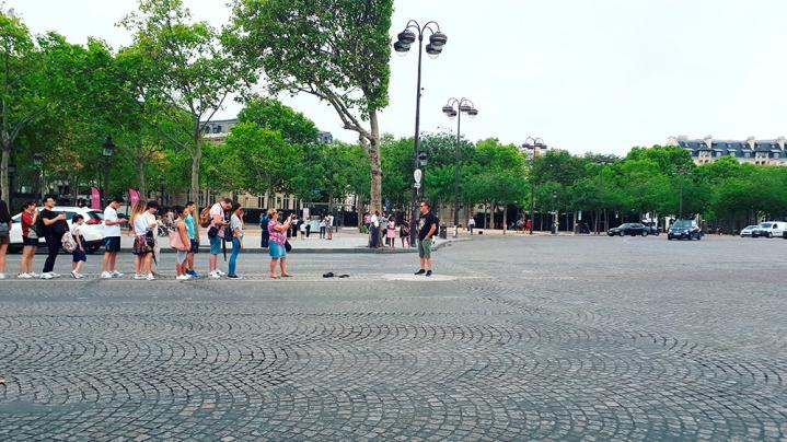 Turisti in fila in mezzo alla strada per fare la foto all'Arc de triomphe