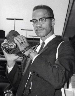 Malcolm X pronto a scattare alcune foto