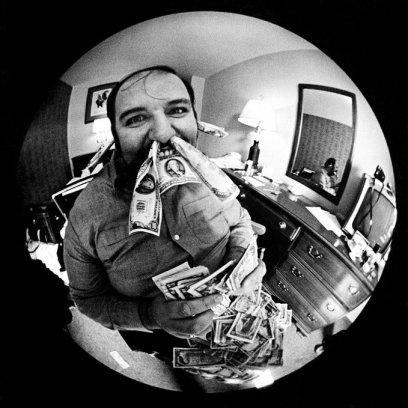Peter Grant fa un selfie con 100 banconote da un dollaro americano infilate nel naso e nelle orecchie. All'epoca era manager dei Led Zeppelin. Foto del 1970