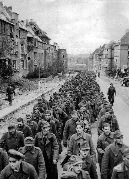 Prigionieri tedeschi, catturati durante la caduta di Aquisgrana, in marcia per le strade in rovina, nell'ottobre 1944