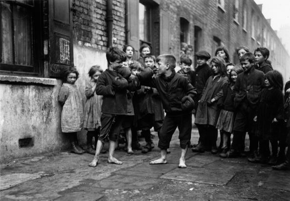 Ragazzi boxano a piedi nudi mentre i loro amici guardano, Londra, 1920