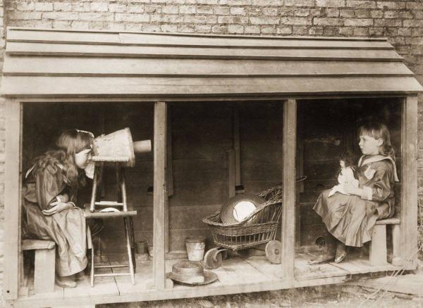 Una bambina usa una macchina fotografica fatta da uno sgabello e un vaso di fiori per fotografare la sua amica, 1887