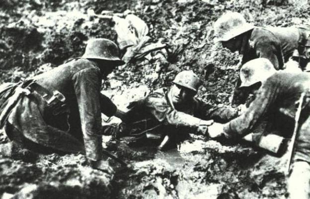 Soldati tedeschi aiutano un francese a uscire da una buca durante la battaglia di Verdun